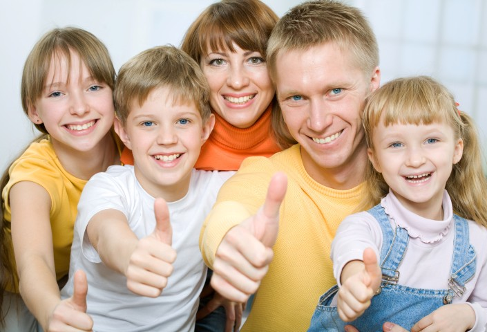 Cheerful family of five with their thumbs up